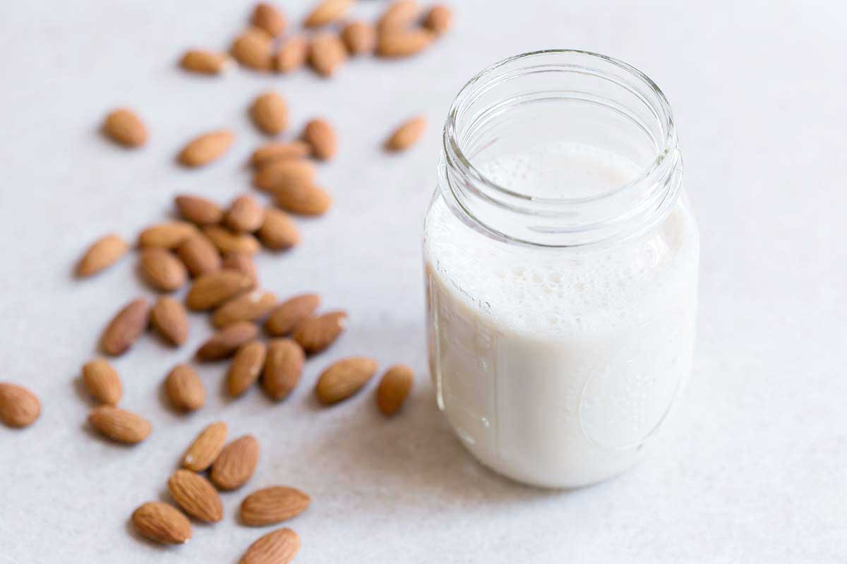 Homemade almond milk in a mason jar on a white backdrop