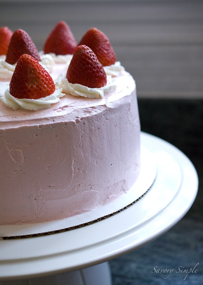 Strawberry Cake on a white stand, topped with whipped cream and fresh strawberries.