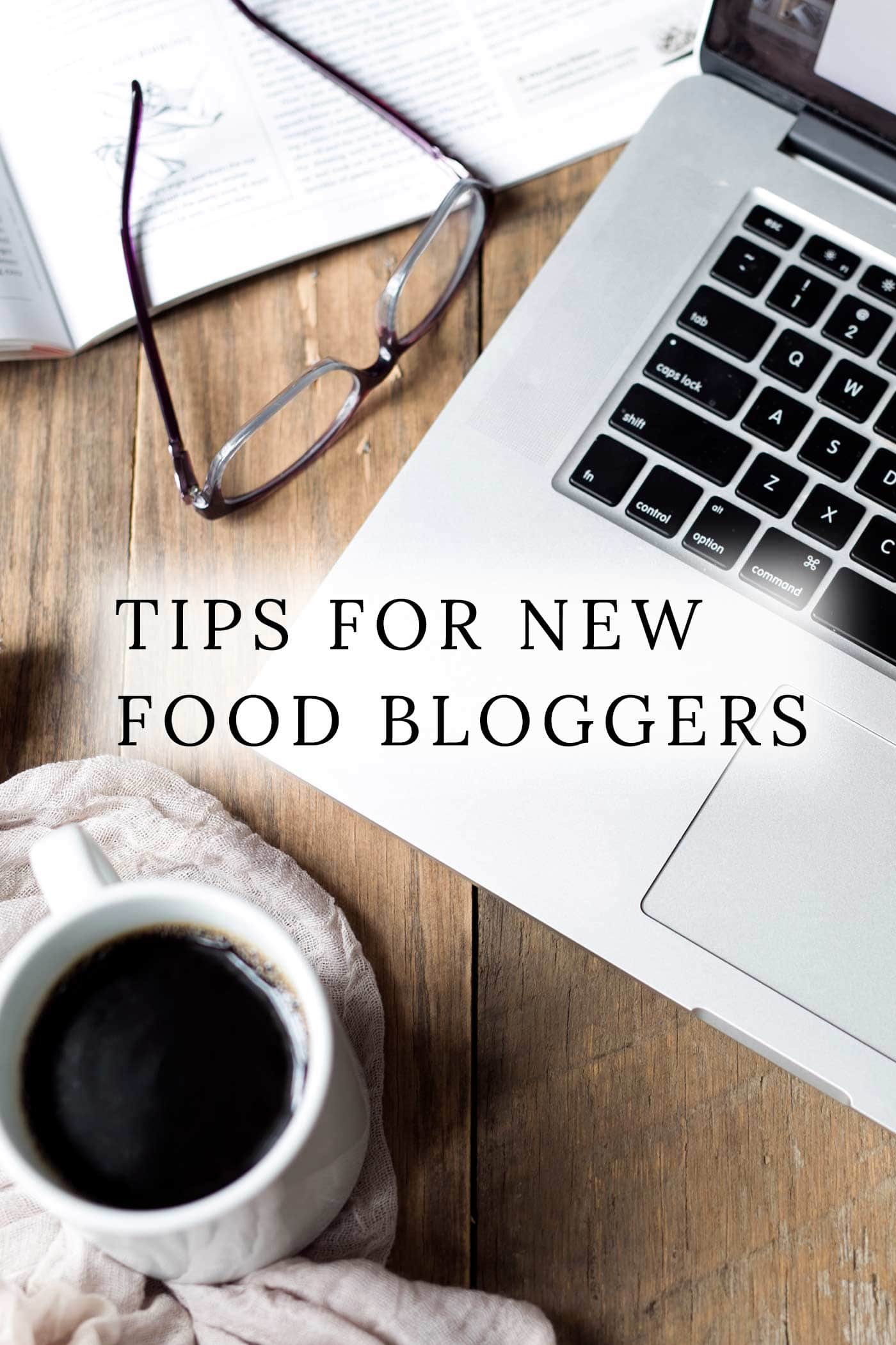 A laptop, coffee, and glasses with text overlay: Food Blogging Tips.