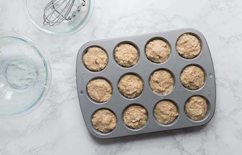 Filling batter for banana bread muffins about 2/3 full.