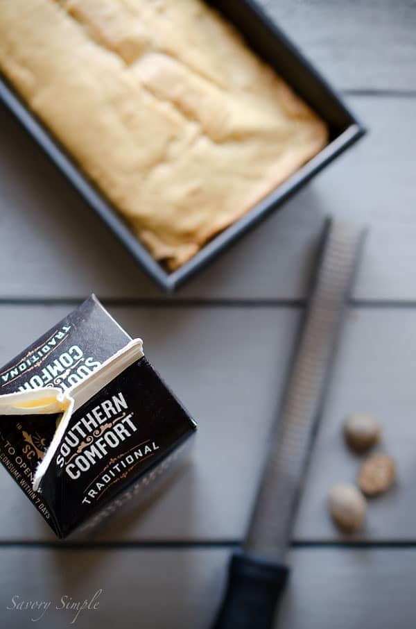 An overhead photo of eggnog pound cake, nutmeg, and Southern Comfort eggnog.