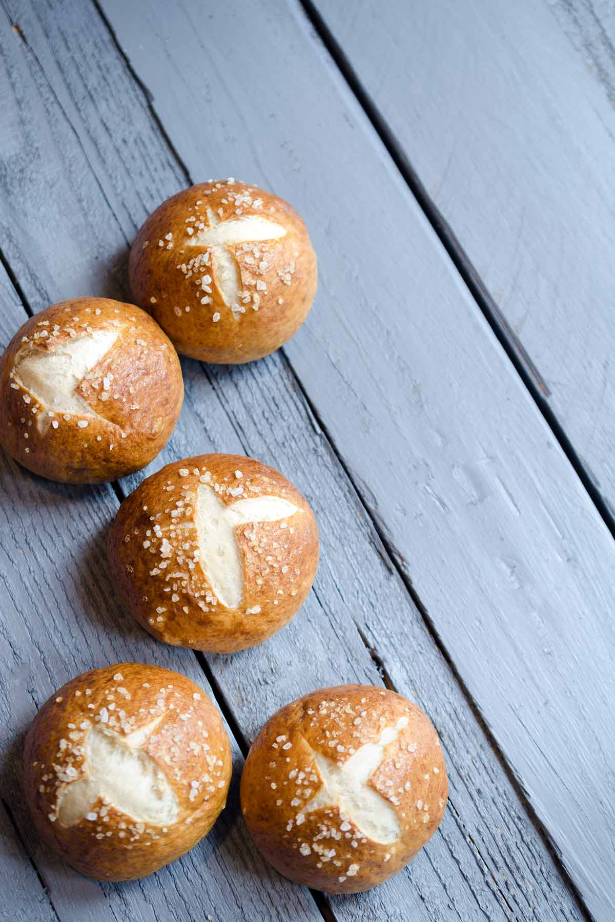 Photo of the finished pretzel bun recipe. Multiple pretzel rolls on a wood backdrop.