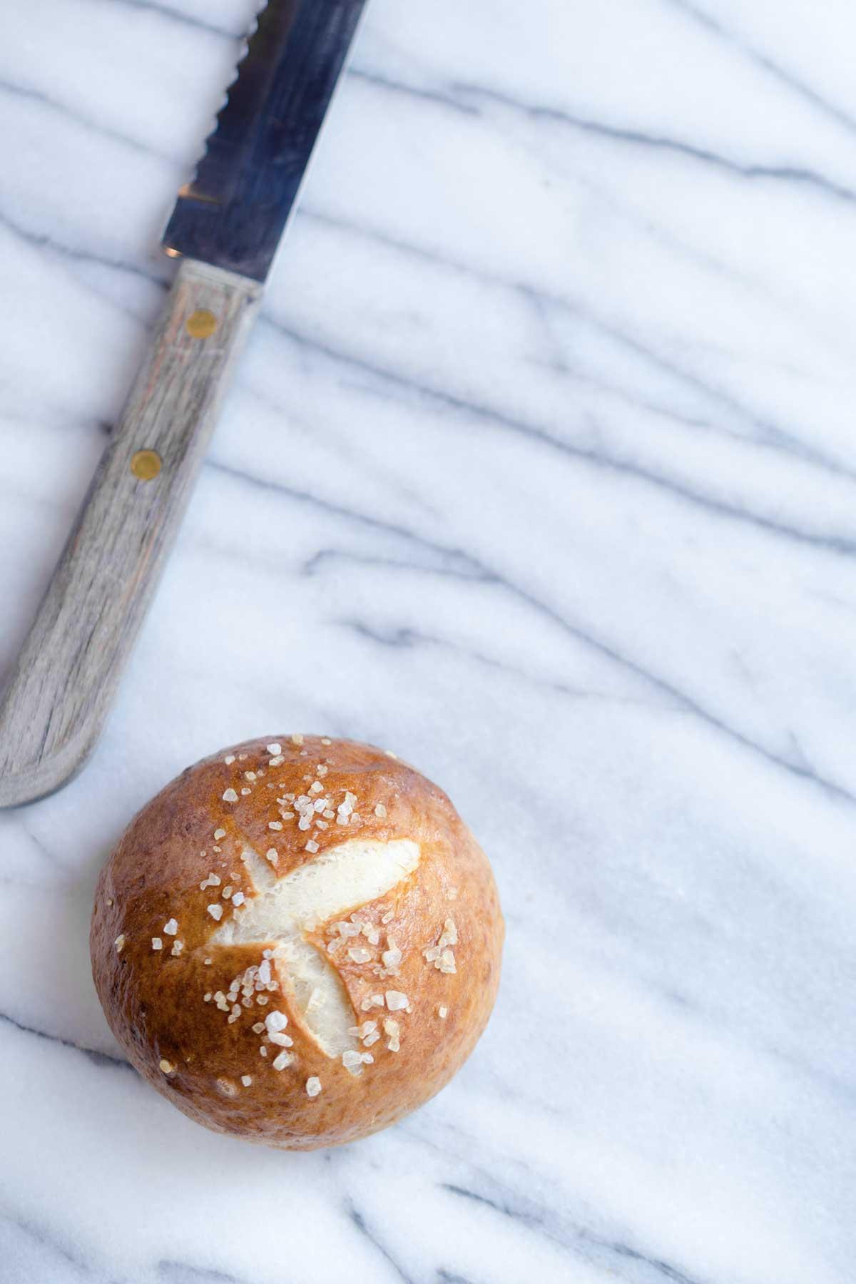 A pretzel bun on a marble backdrop next to a serrated knife.