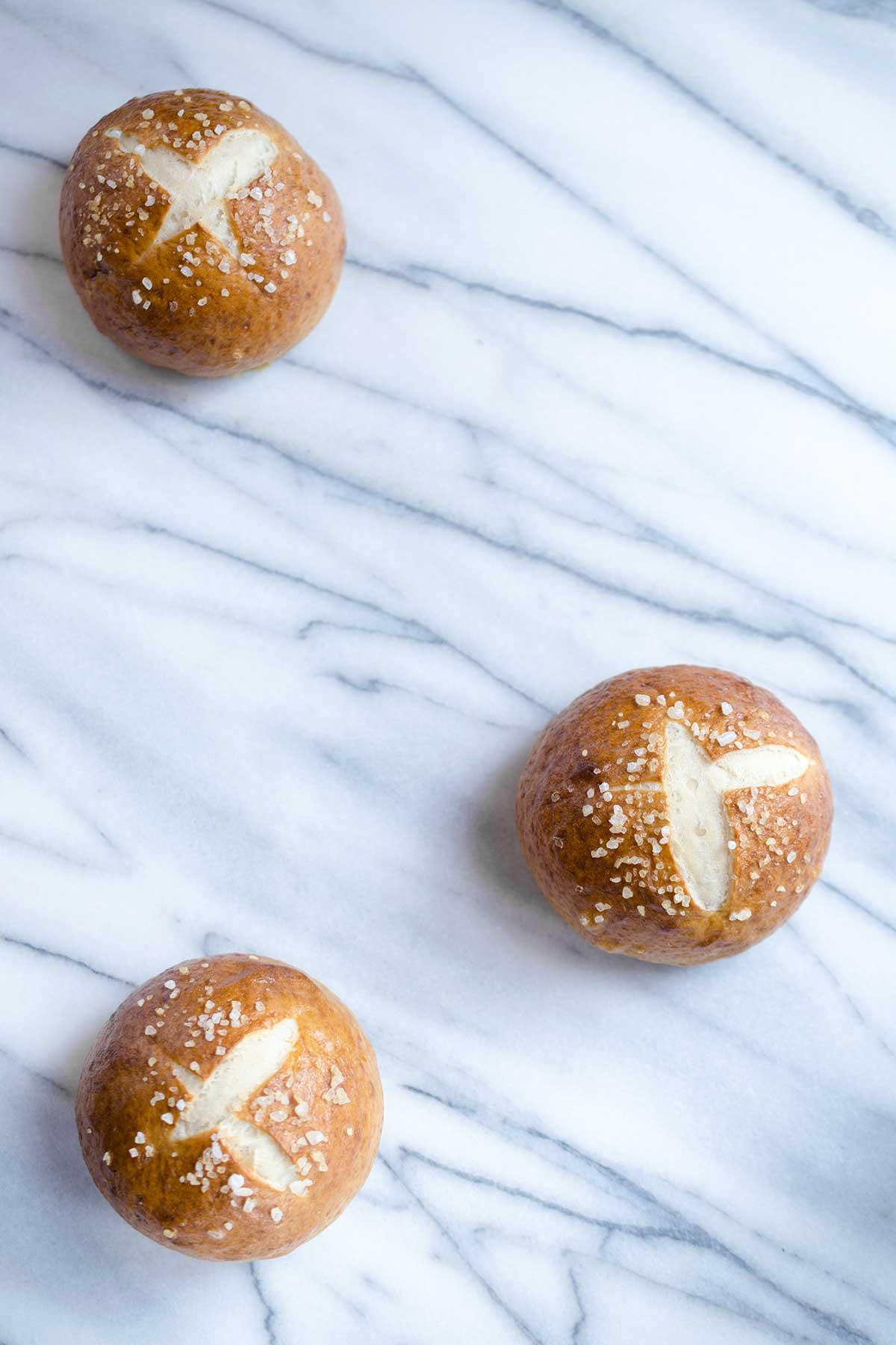 Three pretzel rolls on a marble backdrop.
