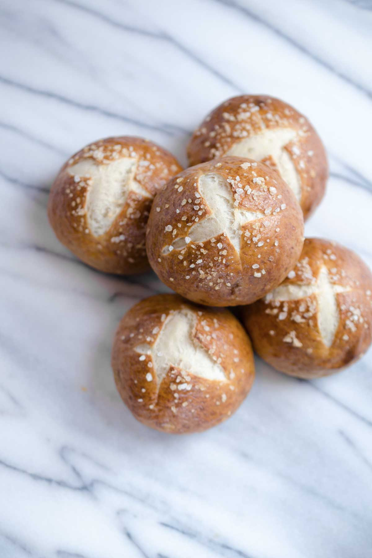 An overhead photo of 5 pretzel buns topped with coarse salt on a marble backdrop.