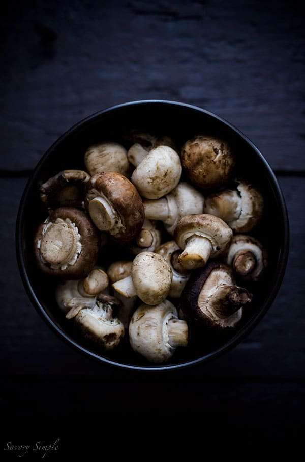 A macro photo of button mushrooms being prepped for asian dumplings.
