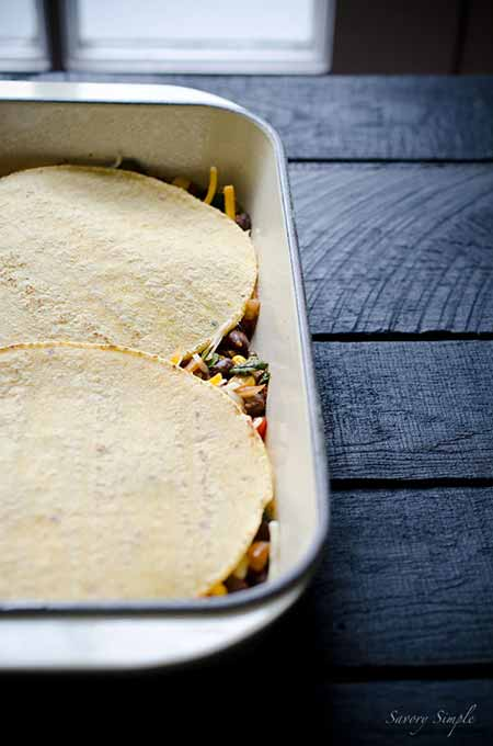A photo of tortilla casserole layers being built up in a casserole dish.