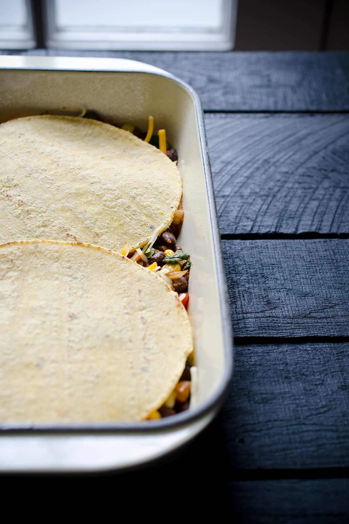 Layers of corn tortillas over tortilla casserole filling.
