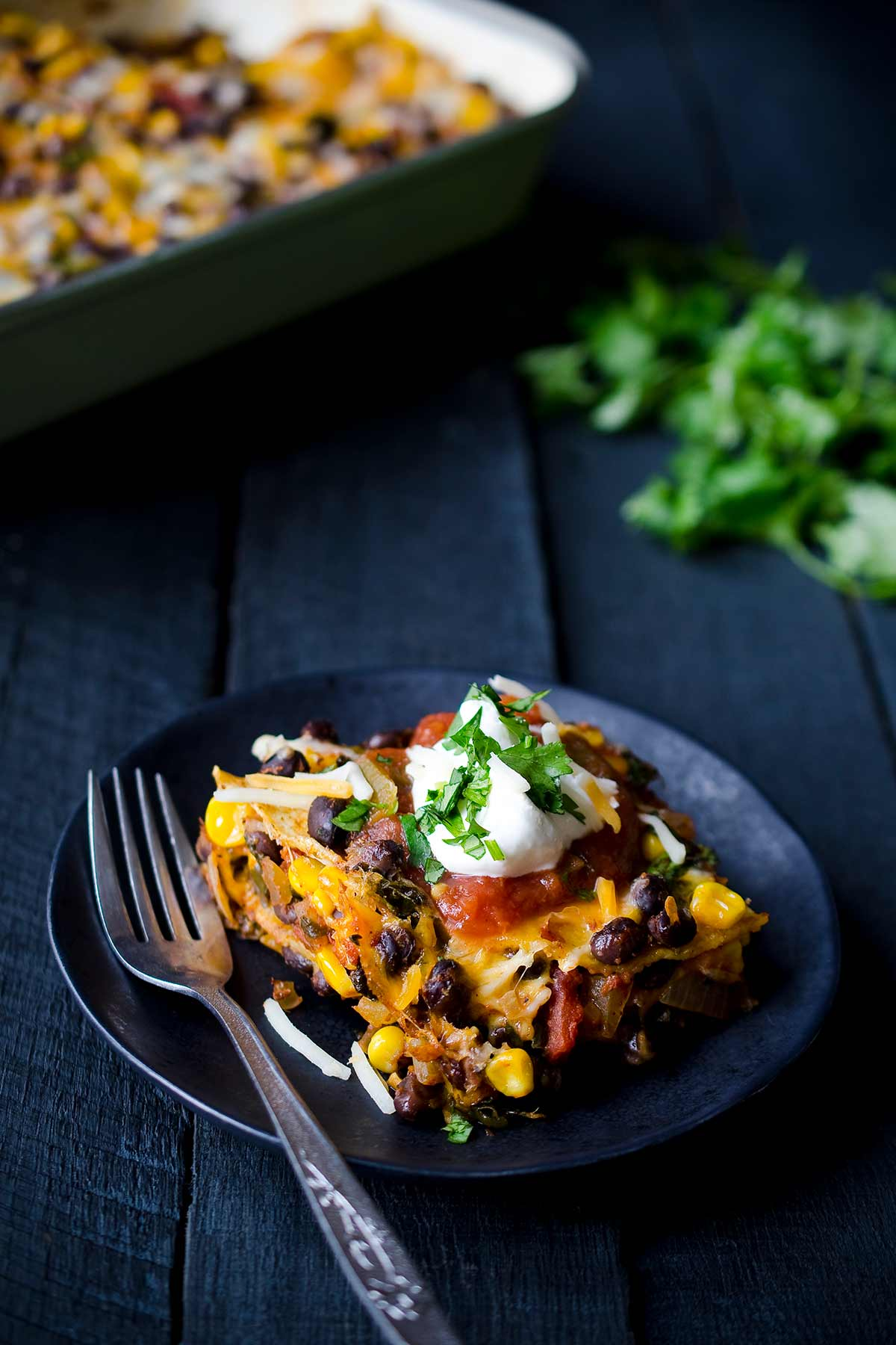 A slice of Mexican tortilla casserole on a plate, topped with sour cream and cilantro.