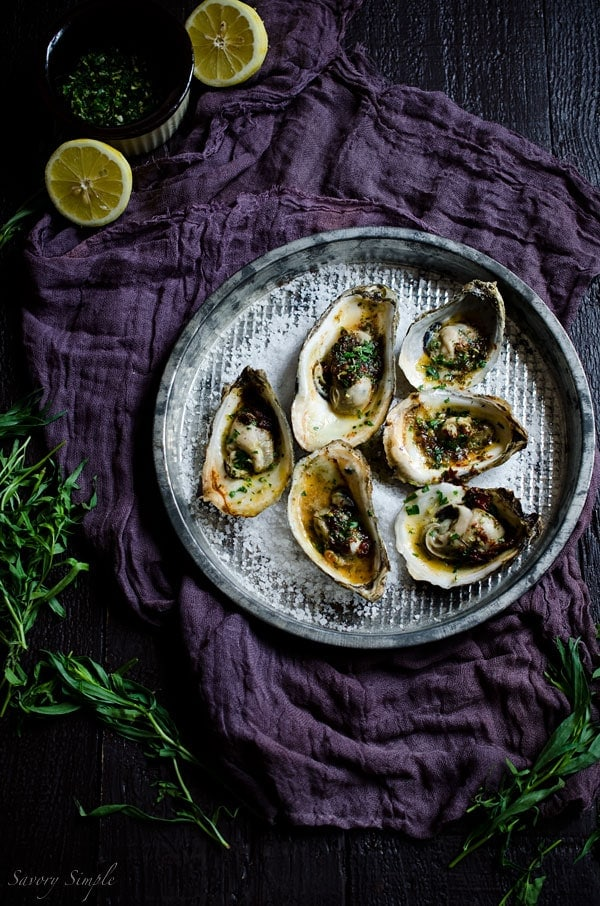 Grilled Oysters with Chipotle Tarragon Butter and Gremolata are a fun and flavorful summer treat! You'll never want plain oysters again! Get the recipe from SavorySimple.net