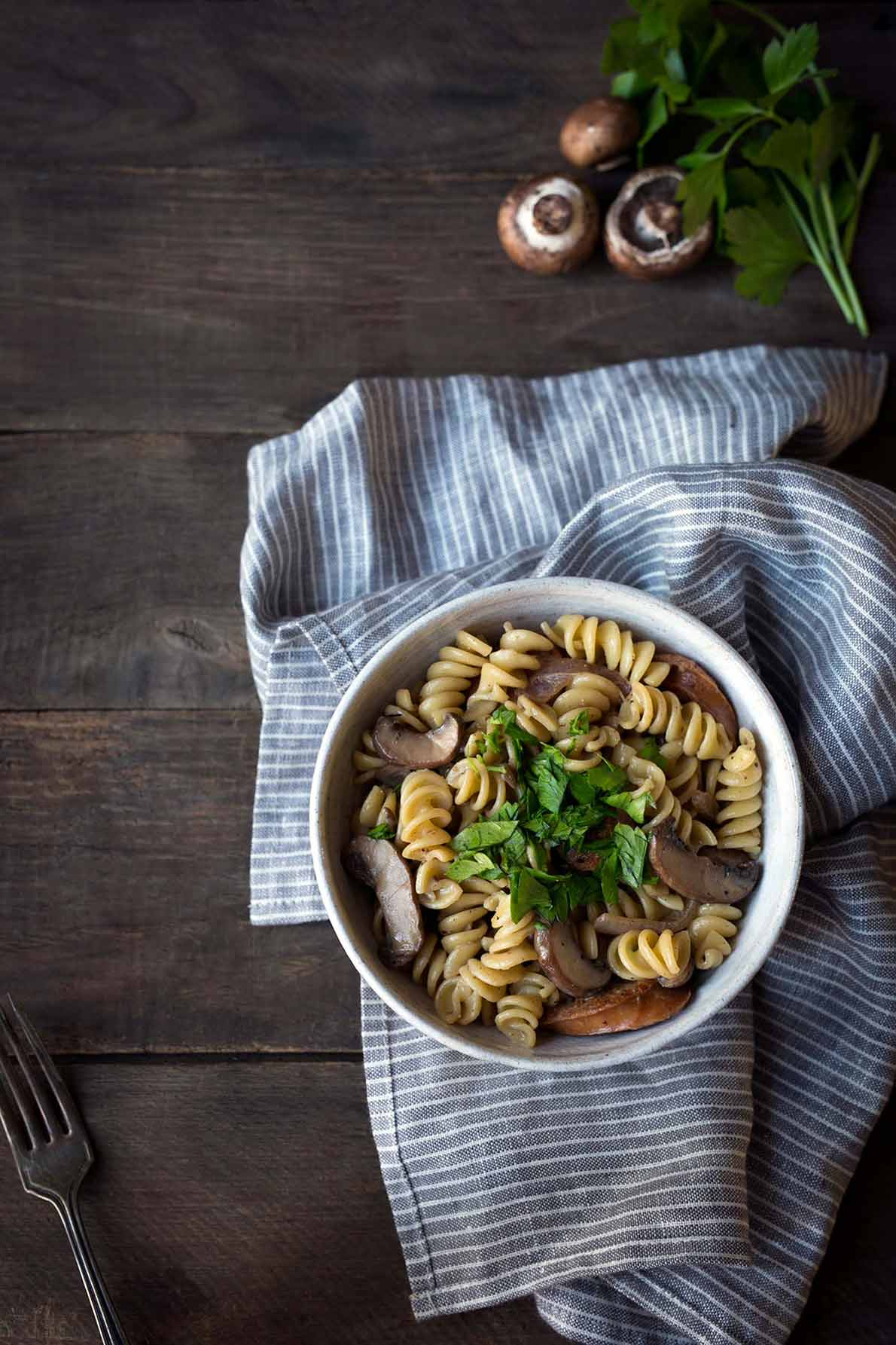 Sausage mushroom pasta in a bowl, sitting on a napkin.