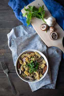 A bowl of sausage mushroom pasta on a napkin, surrounded by a fork, garlic, mushrooms, parsley, and a cutting board.
