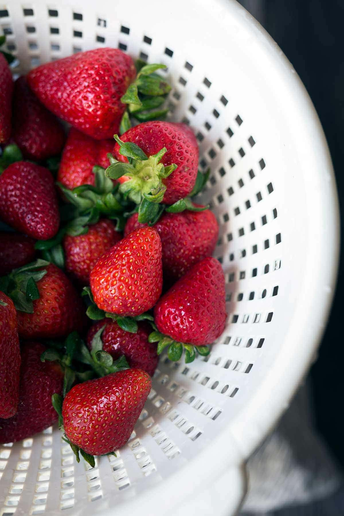 Fresh strawberries with bright green leaves in a white colander.