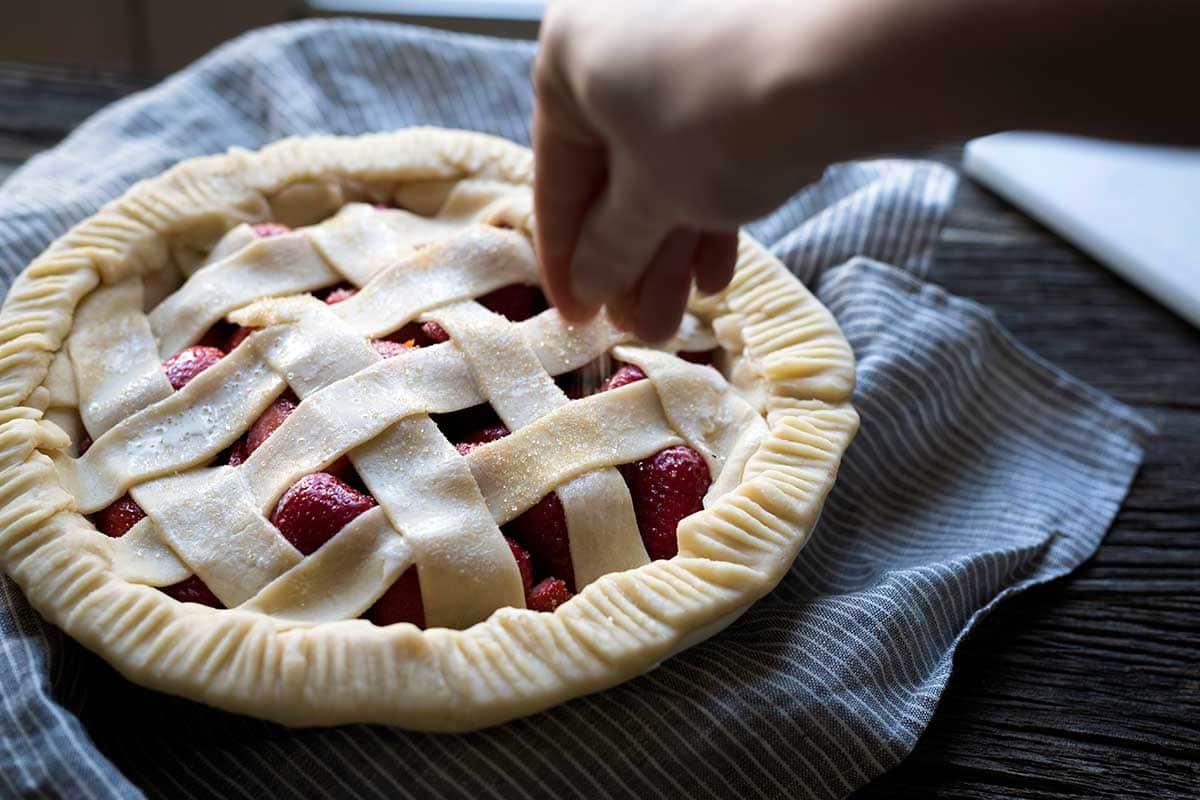 A hand sprinkling coarse sugar over raw pie dough.