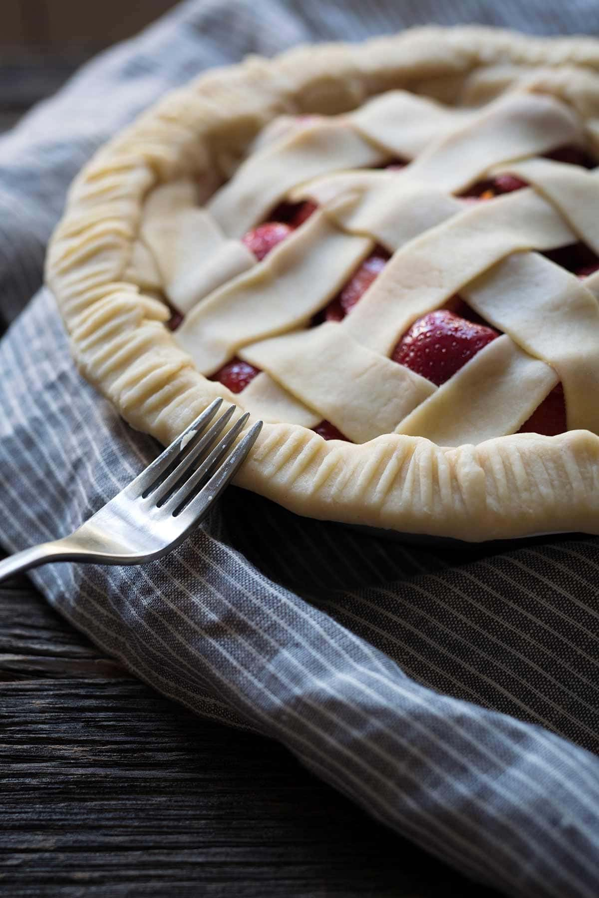 Pressing a fork around the edges of the dough to seal the lattice top edges.