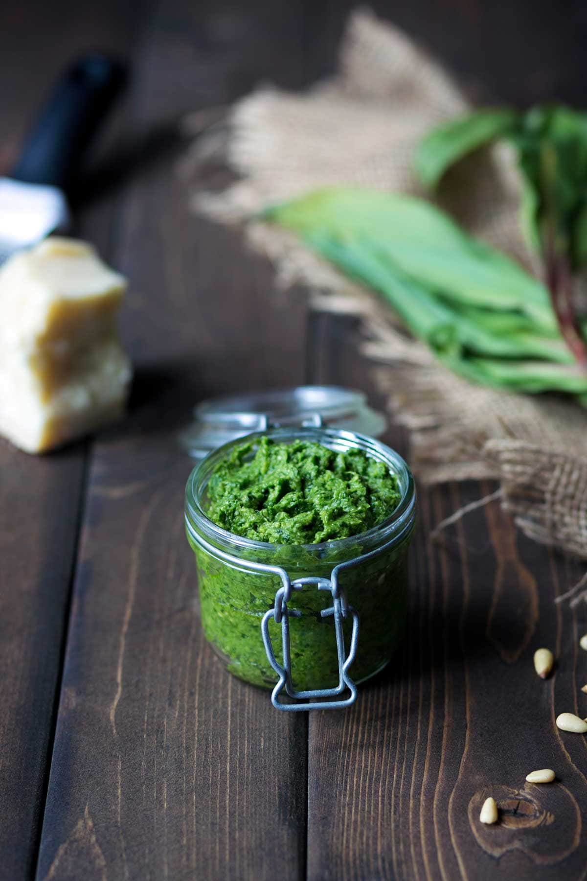Ramp pesto recipe in a mason jar, surrounded by pesto ingredients including parmesan cheese, pine nuts, and ramps.
