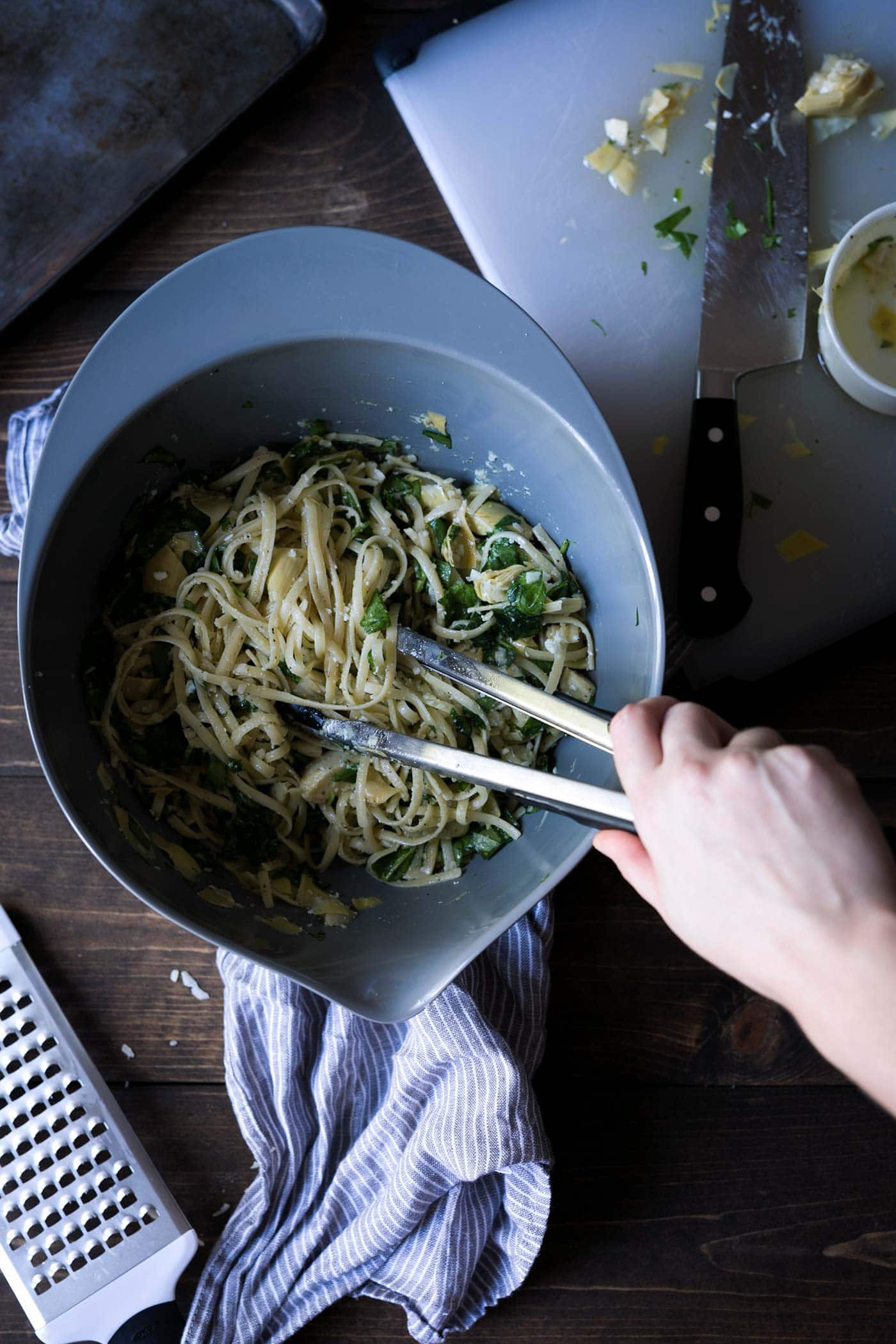 spinach and artichoke pasta ingredients being combined in a bowl