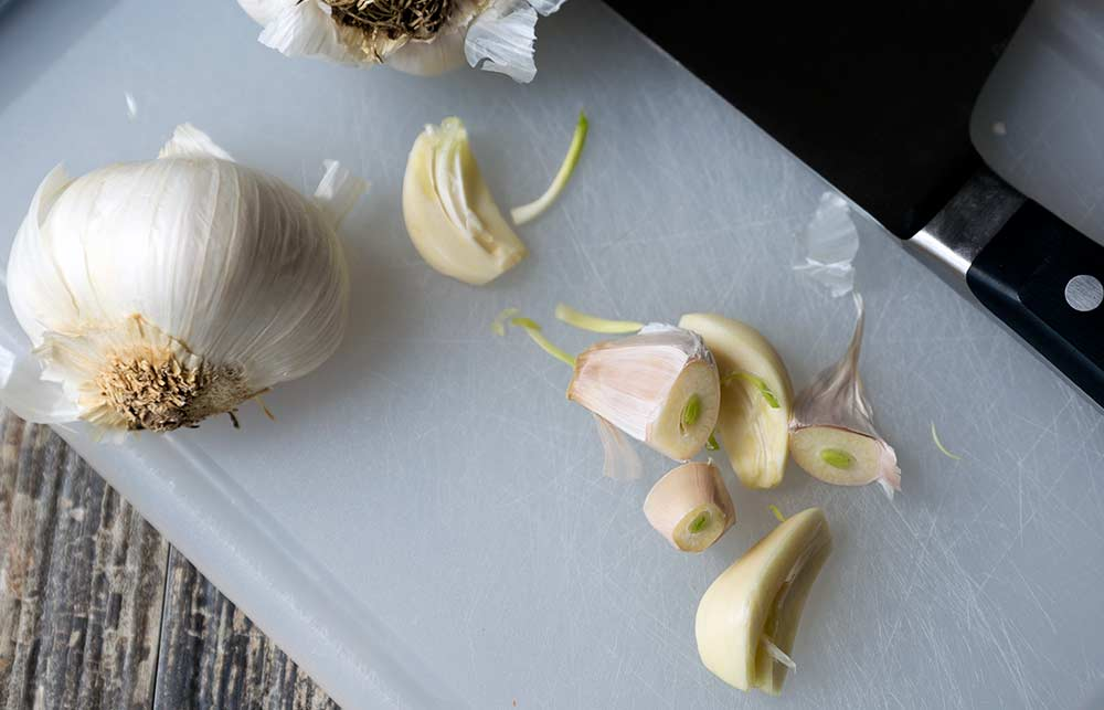 A photo of garlic sprouts, a head of garlic, and a chef's knife.