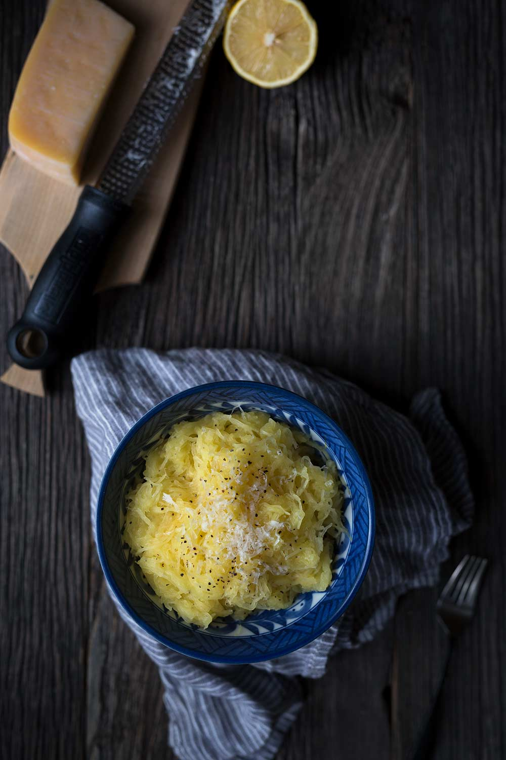 A bowl of Baked Spaghetti Squash with Butter, Parmesan, and Lemon, alongside a block of cheese and half a lemon.