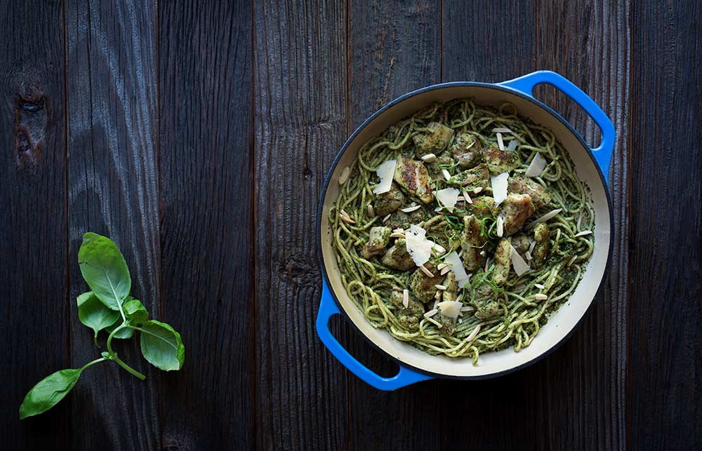 A photo of chicken pesto pasta, garnished with cheese, almonds and basil.