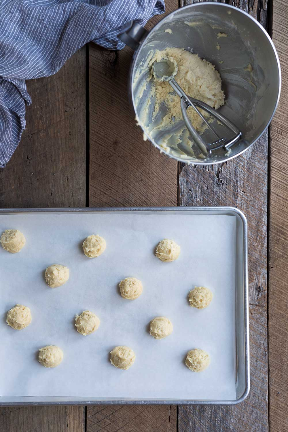 A photo of eggnog cookie dough scooped onto a baking sheet lined with parchment paper.