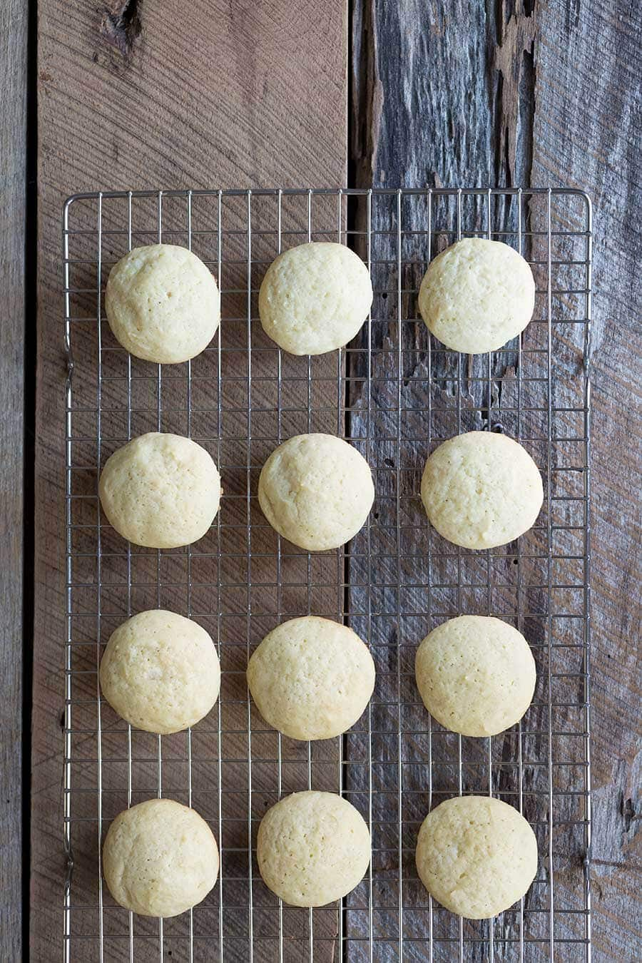 A photo of egg nog cookies cooling on a wire rack, ready to be frosted with eggnog cookie icing.