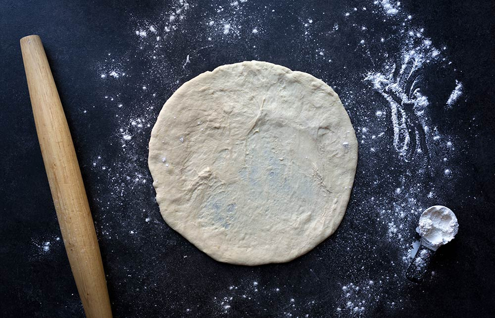 A photo of raw, homemade pizza dough, rolled out and ready to bake.