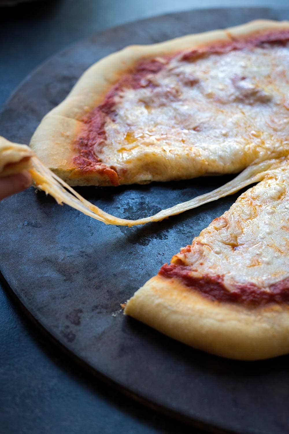 A photo of homemade frozen pizza with melted cheese oozing off a fresh slice.