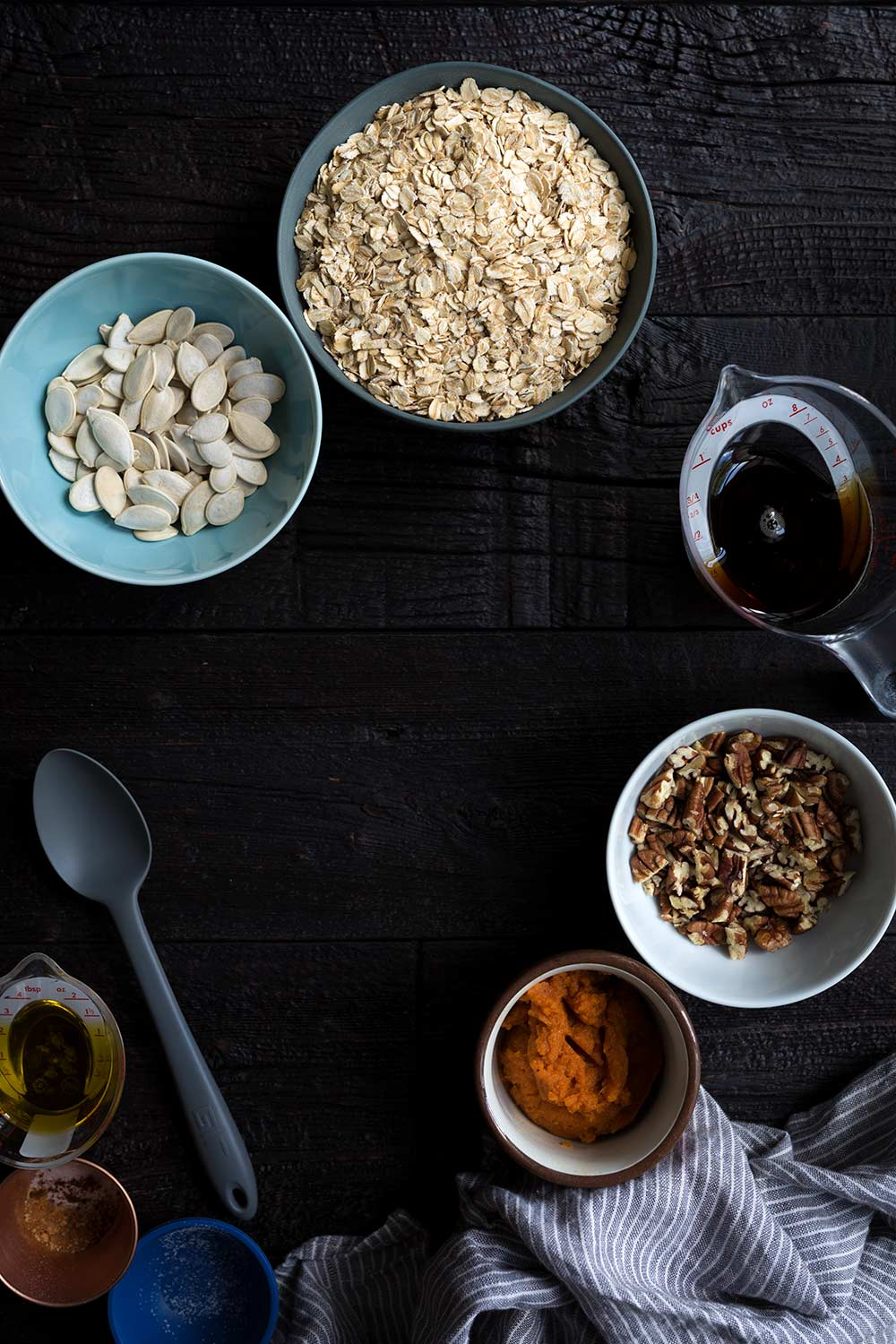 Ingredients to prepare pumpkin granola, including rolled oats, pumpkin seeds, dark amber maple syrup, pecans, pumpkin, and spices.