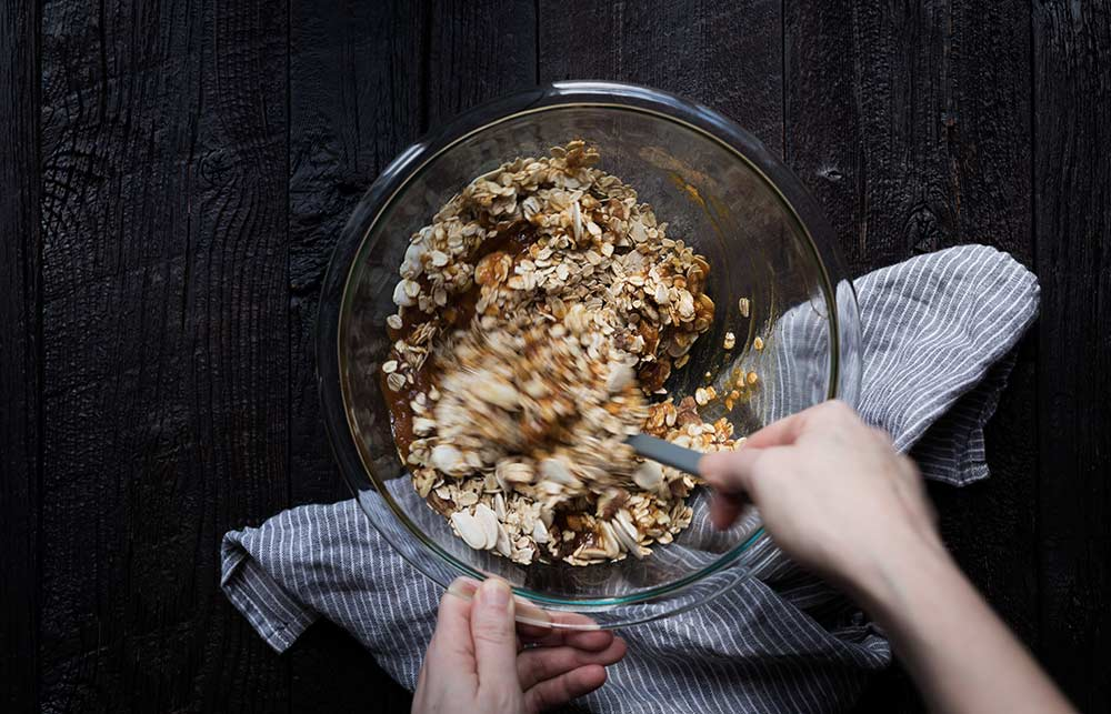 An action shot of granola ingredients being stirred together in a bowl.