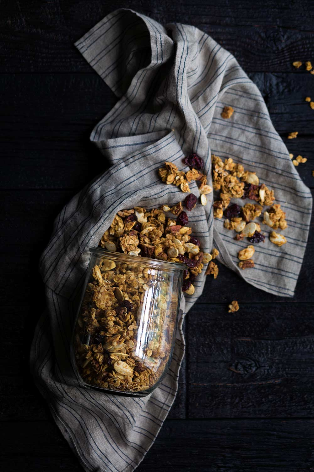 A photo of healthy, homemade pumpkin granola, spilling out of a jar.