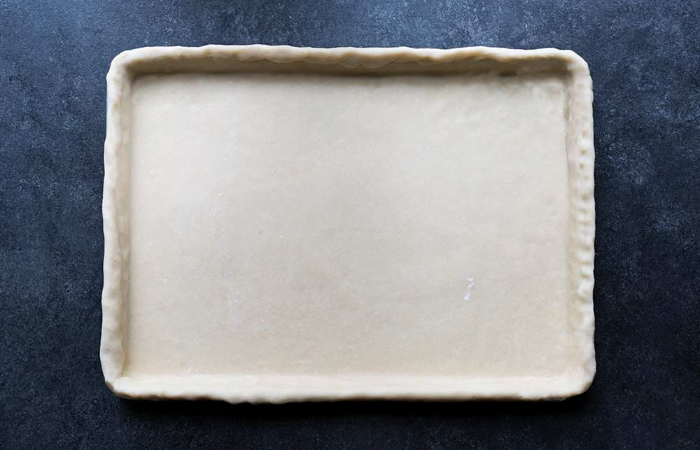 A photo of unbaked pie dough rolled into a sheet pan.