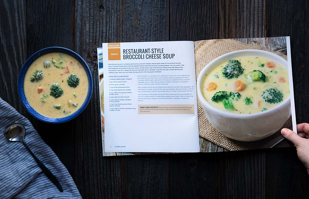 A photo of cheesy broccoli cheddar soup in a bowl next to The Simple Kitchen Cookbook, opened to the page that displays the recipe.