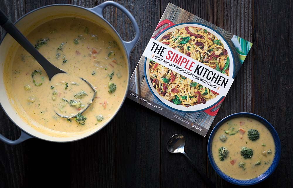 A photo of cheddar broccoli soup is a dutch oven, a bowl, and a photo of the cookbook from which the recipe originated, The Simple Kitchen.