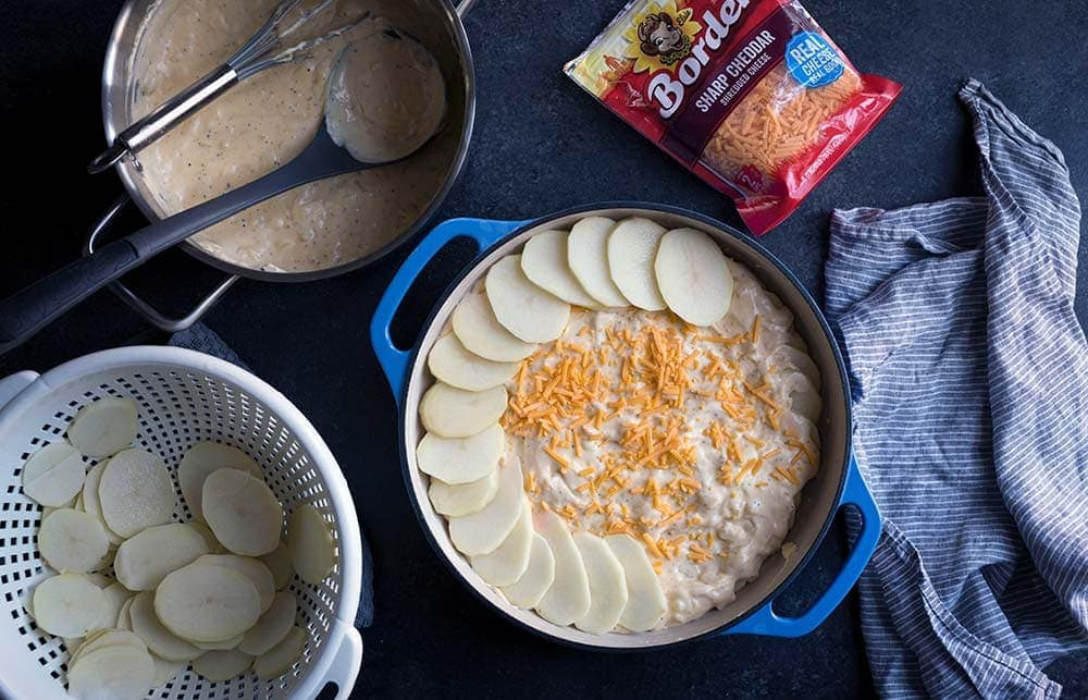 A photo of cheese and potatoes being layered into a casserole dish for au gratin potatoes.