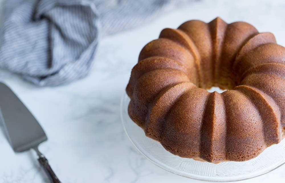 A photo showcasing a whole rum cake from scratch.