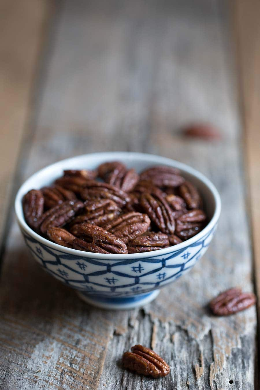 Candied pecans in a small blue and white bowl on a wood backdrop.