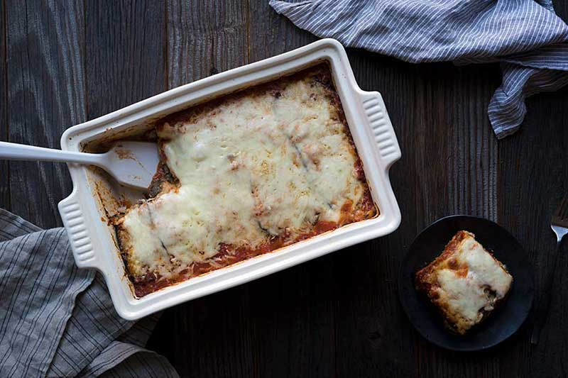 A photo of freshly baked eggplant mushroom lasagna, with one slice served up on a plate.