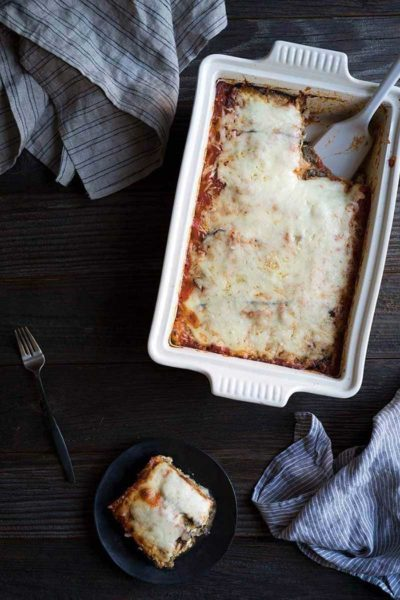 Eggplant lasagna recipe in a casserole dish with one slice on a plate
