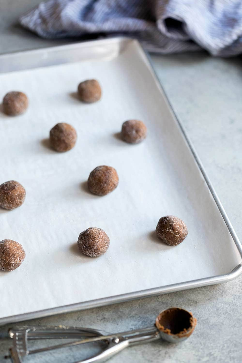 Gingerbread cookie dough scooped into balls on a cookie sheet
