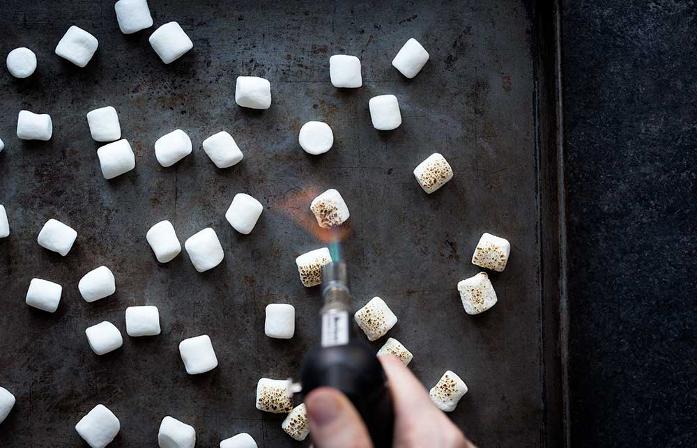 A photo of marshmallows being toasted for a smores dessert