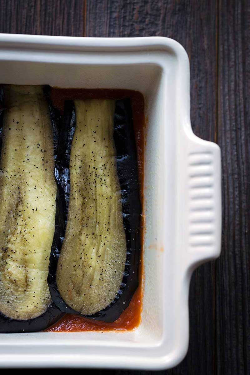 A photo of sliced, roasted eggplant being layered in a casserole dish.