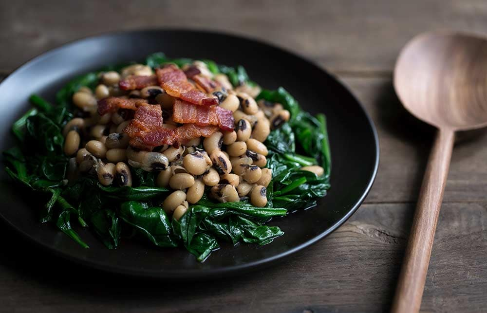 A photo of the finished dish of black eyed peas with spinach and bacon.