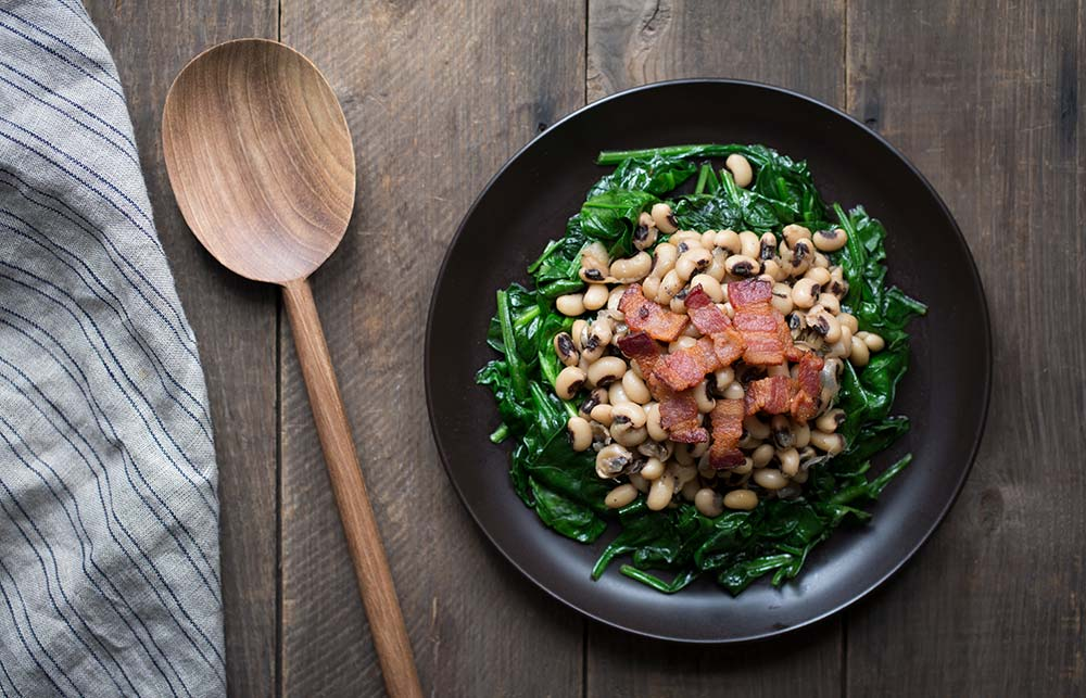 A photo of the finished black eyed peas with spinach and bacon on a plate to serve.