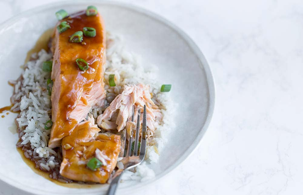 A photo of flavorful salmon teriyaki being cut with a fork.