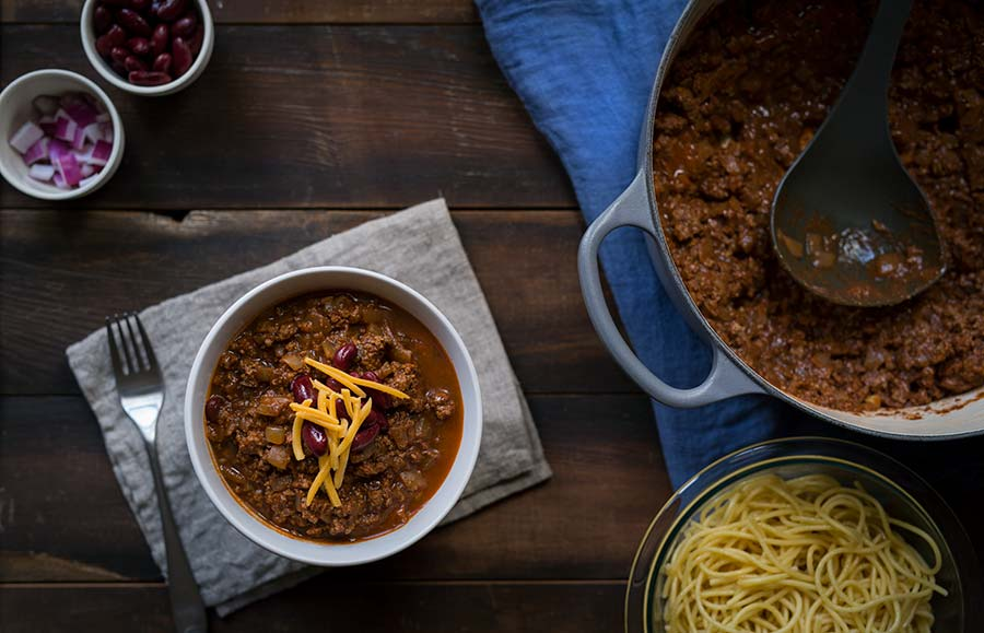 Cincinnati chili in a bowl, topped with garnishes.