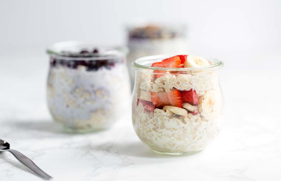 A close up of overnight oats in a jar mixed with strawberries and bananas.
