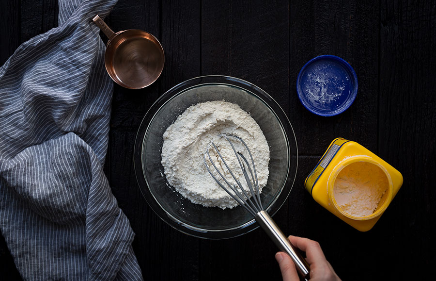A bowl of flour being whisked.