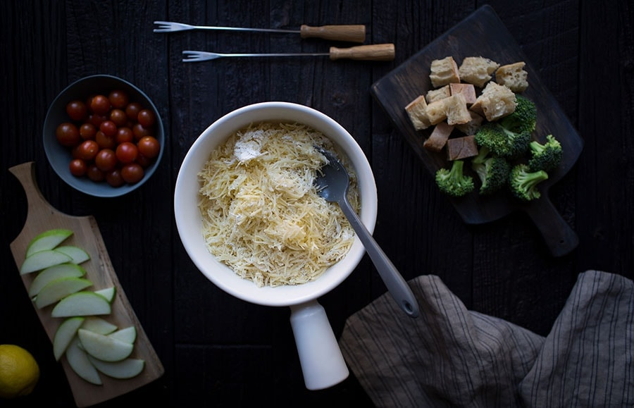 A photo of grated cheese in a fondue pot.