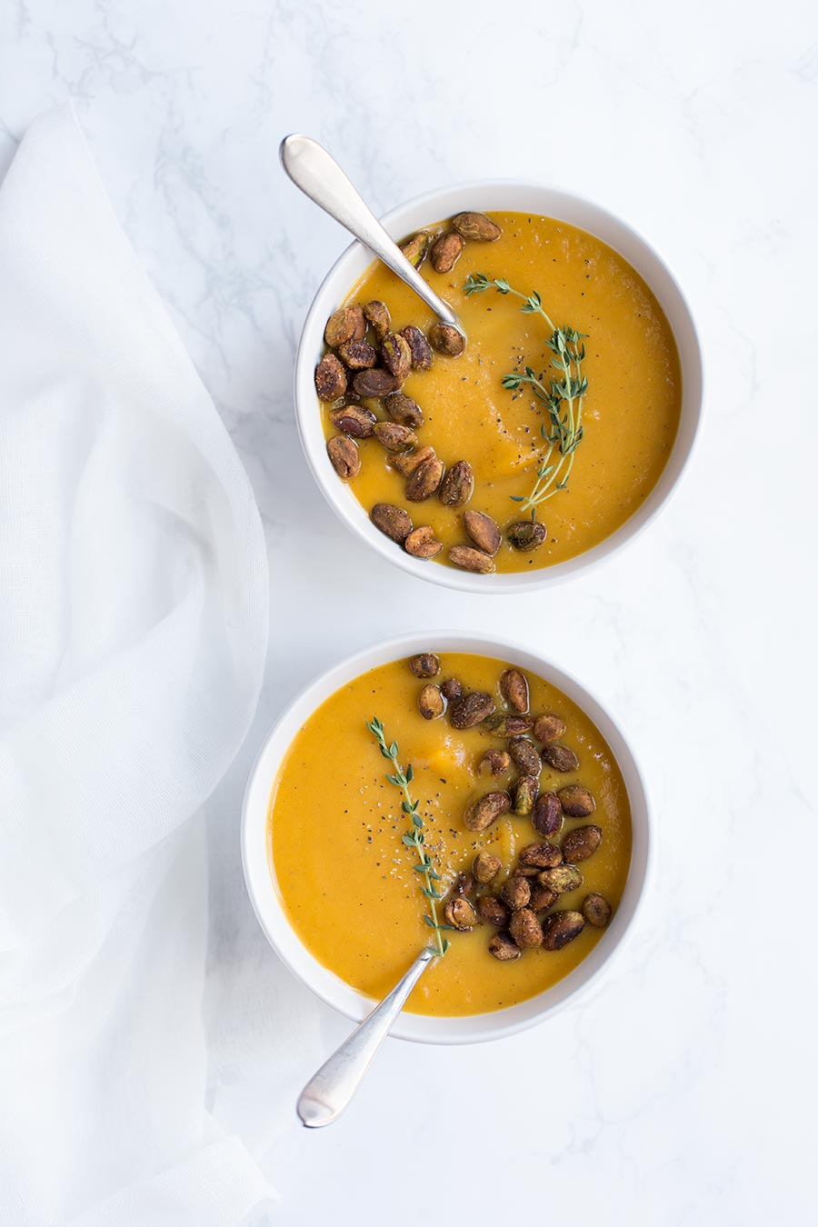An overhead shot of vegan butternut squash soup garnished with nuts and thyme.